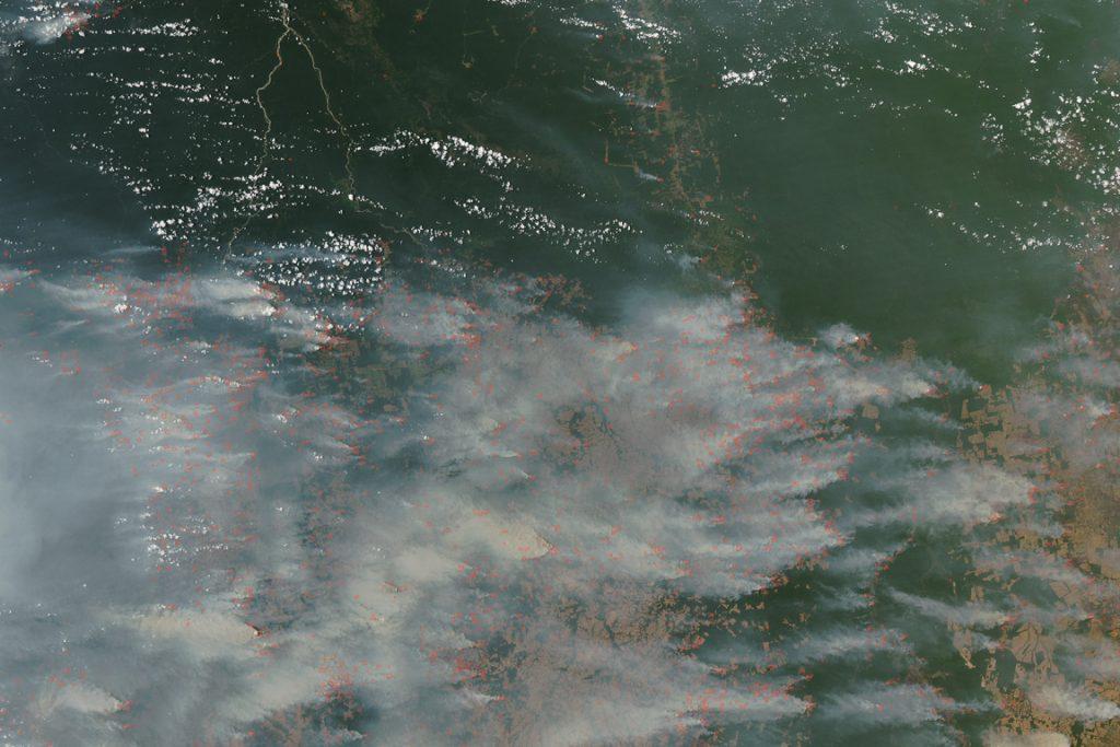Extensa área da Amazônia coberta por fumaça de queimadas. Os pontos vermelhos indicam áreas com fogo ativo. As nuvens são as estruturas arredondadas brancas. Setembro de 2007. Imagem é cortesia de MODIS Rapid Response Team no Goddard Space Flight Center da Nasa.