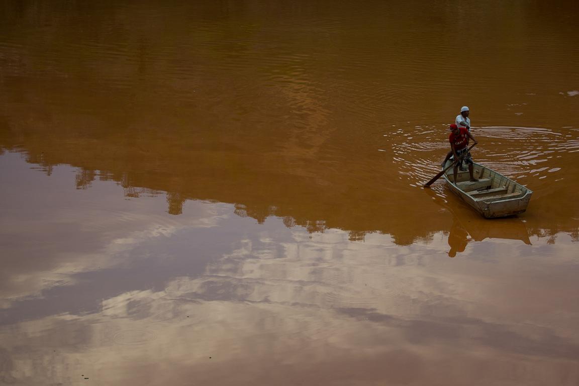 Moradores ribeirinhos tentam atravessar trecho do rio Doce em um barco na cidade de Governador Valadares, MG.