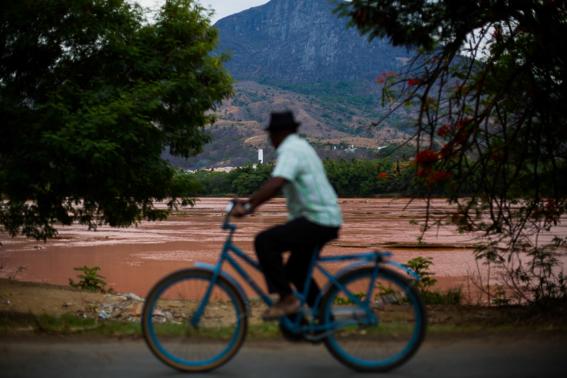 Ao passar de bicicleta, morador observa o estrago no Rio Doce, na cidade de Governador Valadares.