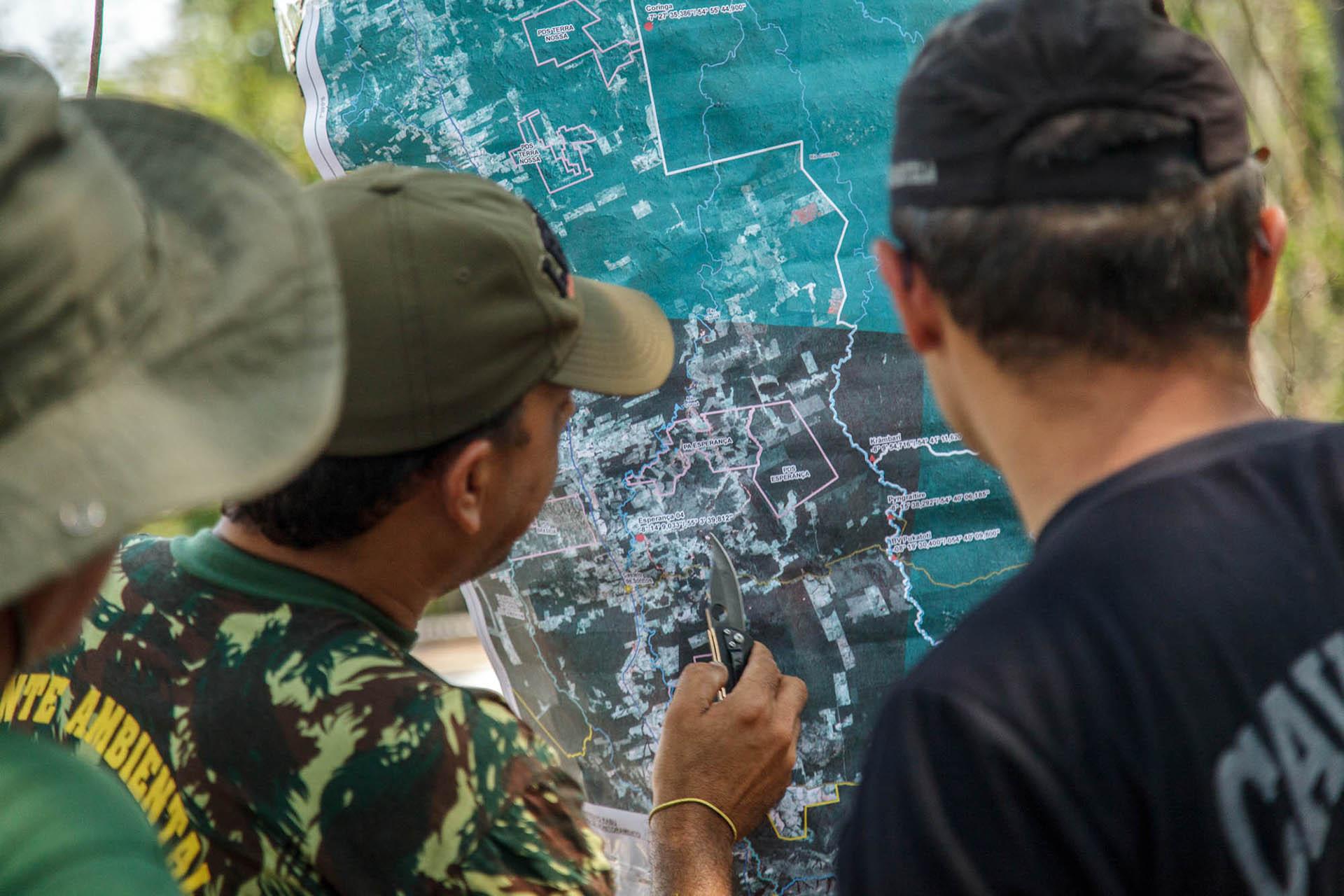 Servidores do IBAMA e indígenas observam o mapa dos arredores da TI Mekrãgnoti