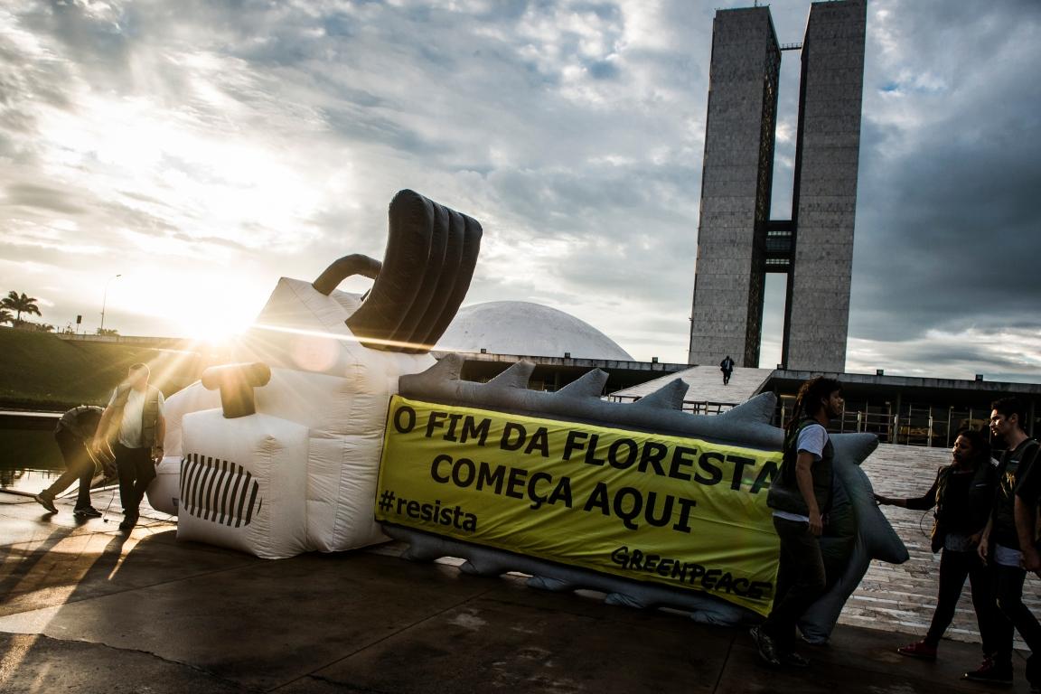 """Durante a manhã, ativistas do greenpeace protestaram do lado de fora do Congresso. Uma faixa escrita """"O fim da floresta começa aqui"""" cobriu parte de uma motosserra inflável. Foto:© Leonardo Milano / Greenpeace."""