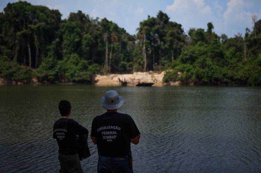 Às margens do Rio Jamanxim, fiscais do ICMBio observam balsa usada para retirada ilegal de madeira. Foto: Bernardo Camara