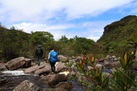 Trilha cruza o rio, com paredão rochoso no horizonte. Foto: Duda Menegassi.